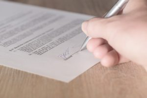Eine Hand mit einem Kugelschreiber in der Hand, die einen Vertrag unterzeichnet