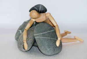 Ein Holzmännchen, dass über Steine liegt und auf dessen Kreuz ein Stein liegt.