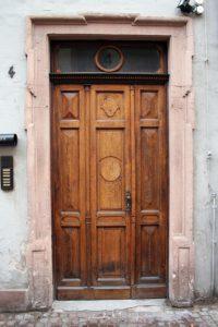 Eine Holztüre, links davon befindet sich eine Klingel und eine Zeitungsrolle