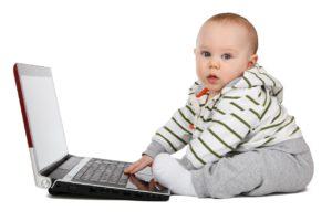 Ein Baby, das vor einem Laptop sitzt