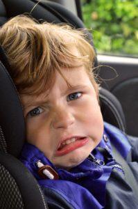Ein Kind im Auto Kindersitz mit quengelndem Gesicht.
