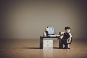 Ein Lego-Schreibtsich vor dem ein Legomännchen sitzt und kritisch schaut.