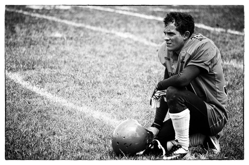Ein Schwarzweißbild von einem Football-Spieler der nach einer Niederlage auf dem Boden kniet