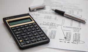 Im Vordergrund ein Taschenrechner im Hintergrund Papiere mit Rechnungen und ein Kugelschreiber