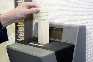 Jemand stempelt seine Stempelkarte ab zum Arbeitsnachweis