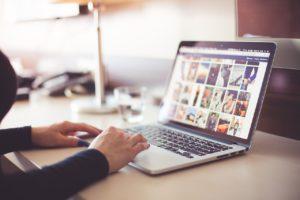 Hände auf dem Laptop, auf dem Monitor sind mehrere Bilder zu sehen