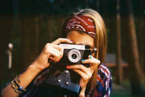Eine Frau, die mit einer Retro-Kamera photographiert.