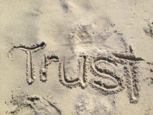 In Sand gezeichneter Trust-Schriftzug für Vertrauen