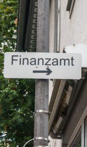Eine Straßenlaterne auf der ein Schild mit der Aufschrift Finanzamt hängt.
