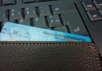 Eine Krankenkassenkarte, die aus einem Geldbeutel herausschaut, der auf einer Tastatur liegt.