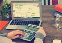 Jemand der auf einen Taschenrechner tippt und ein Laptop vor sich stehen hat, auf dem eine Rechnung angezeigt wird