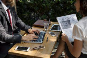 Zwei Personen die draußen im Kaffee sitzen und arbeiten