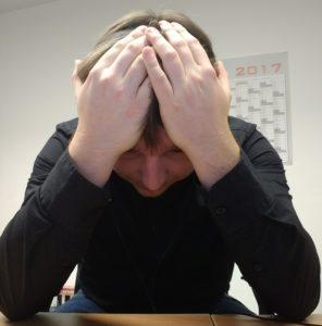 Ich wie ich mir am Schreibtisch sitzend die Hände über den Kopf schlage