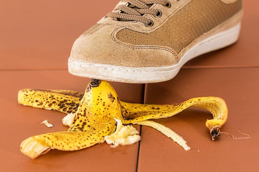 Ein Fuß der kurz davor ist auf eine Bananenschale, die auf dem Boden liegt, auszurutschen