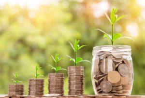 Finanzieller Erfolg: vier kleine Geldhaufen, die in einen großen Münden.