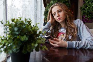 Eine Frau die gelangweilt am Tisch sitzt und ihr Smartphone in der Hand hält
