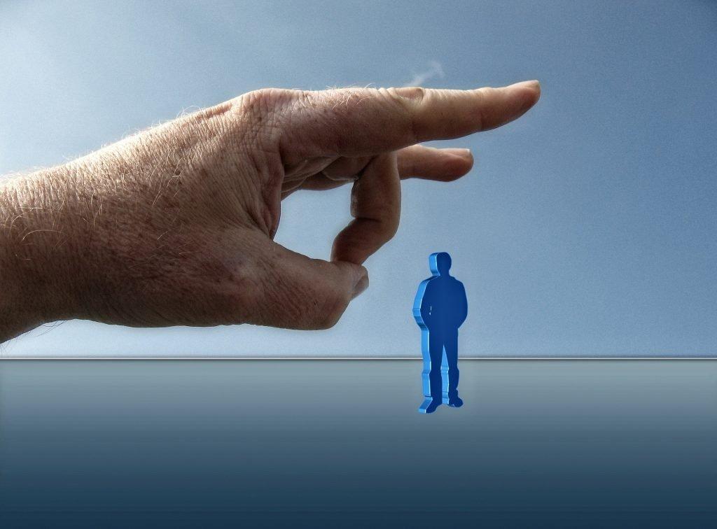 Ein großer Finger, der einen Menschen wegschnippst