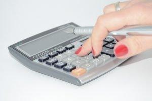 Eine Frauenhand, die einen Taschenrechner bedient und etwas ausrechnet.