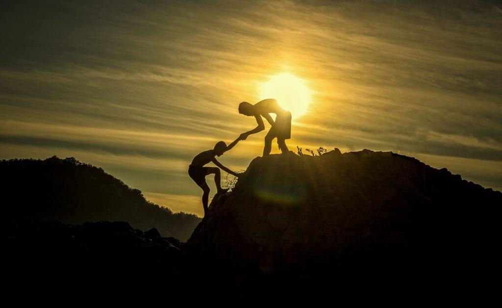 Ein Junge hilft dem anderen den Berg hoch.