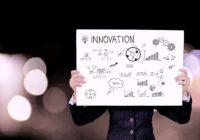 Ein Business-Mann hät ein Schild mit der Aufschrift Innovation und innovative Zeichnungen hoch