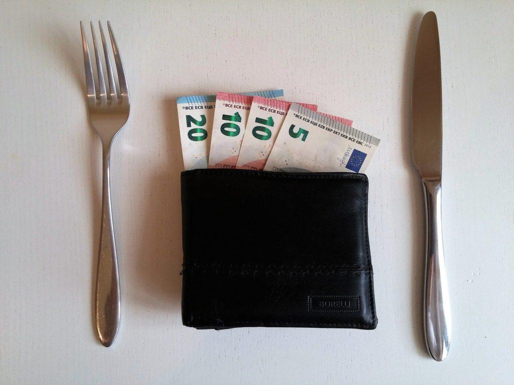 Geldscheine im Geldbeutel, daneben Messer und Gabel als Sinnbild für Arbeitslohn