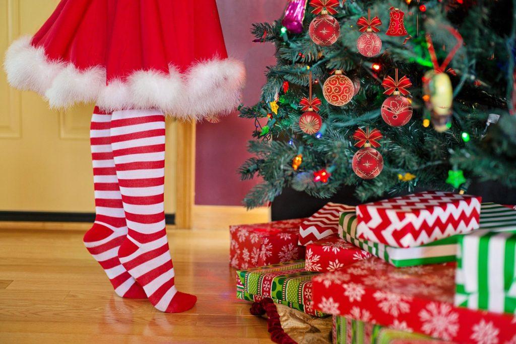 Geschenke unterm Weihnachtsbaum davor steht ein Kind, wo nur die Beine zu sehen sind