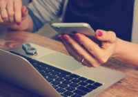 Eine Person sitzt am Schreibtisch vor dem PC und hält ein Smartphone in der Hand