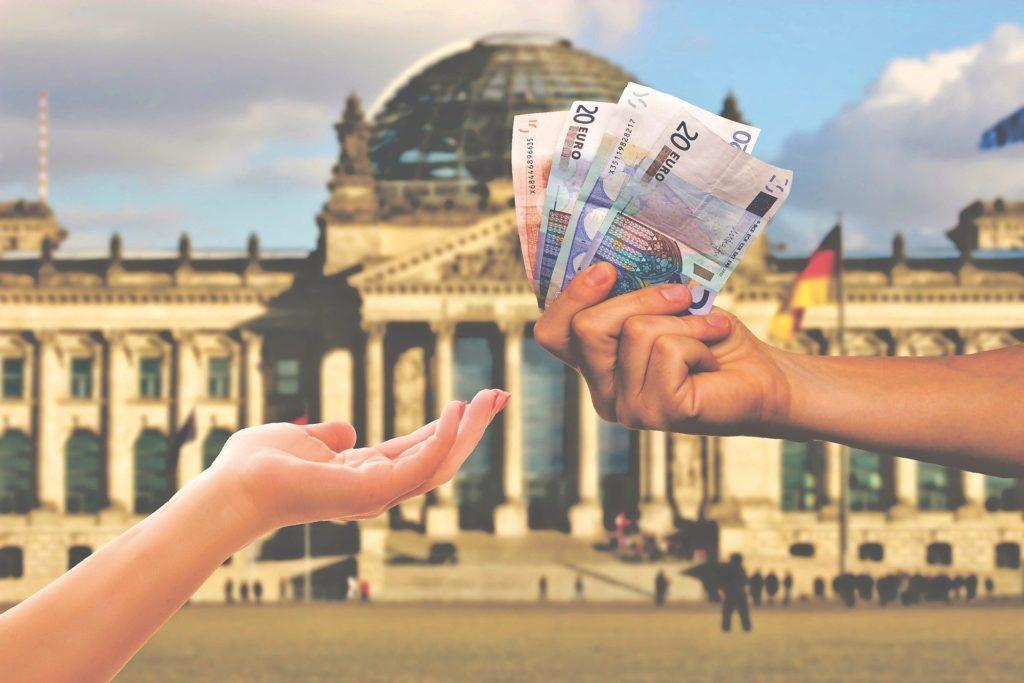 Jemand reicht einem anderen Geld im Hintergrund der deutsche Bundestag