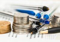 Münzen liegen neben Stiften auf einem Antrag