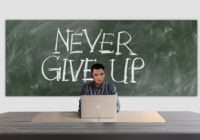 """StartUp Mensch sitzt vor der Tafel, auf der steht """"Never Give Up"""""""
