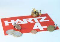 """Schild bedruckt mit """"Hartz IV"""" und Euromünzen"""