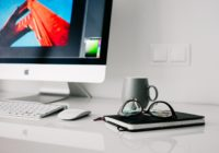 Schreibtisch mit PC, auf dem gerade ein Bildbearbeitungstool offen ist