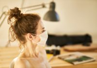 Eine Frau trägt eine Maske in ihrem Büro