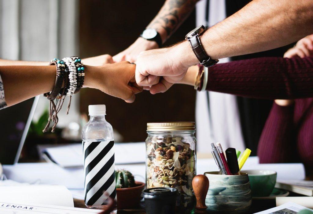 Menschen klatschen sich mit geballter Faust ab, um Teamfähigkeit zu symbolisieren.